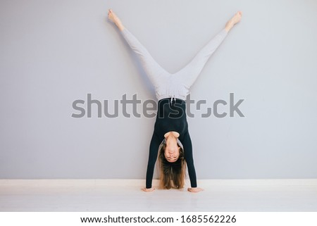 Fit woman doing handstand near empty grey wall at home. Athlete standing on hands Concept balance sport fitness