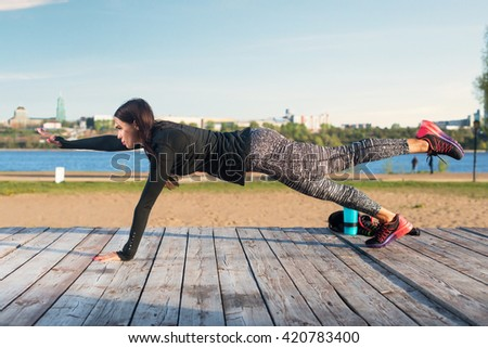 Fit woman doing raised leg plank yoga pilates exercises training her abs core muscles outdoors