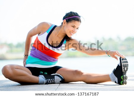 Fit woman doing stretching exercises outdoors and smiling