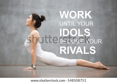 "Fit woman doing yoga or pilates exercise. Fitness motivation quote with motivational text ""Work until your idols become your rivals"". Healthy lifestyle concept. Upward facing dog pose"