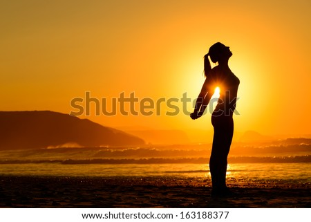 Fit Woman Doing Yoga Relaxing And Breathing Exercises On Beach At Sunset. Freedom, Relax And Harmony In Nature. Female Stretching Arms Alone.