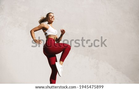 Fit woman exercising outdoors. Healthy young female athlete doing fitness workout. Sportswoman raising leg, do functional training outside on bright sunny day, smiling pleased, wearing sport outfit