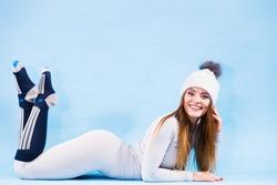 Fit woman in full length wearing winter cap, gray sports thermal underwear, warm socks studio shot on blue. Long sleeves top and leggings.