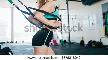 Fit woman in sport wear exercises with fitness straps close-up in the gym. Functional training Stock foto ©