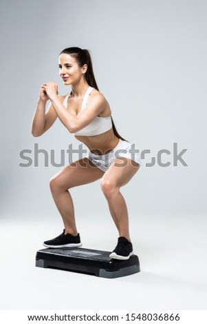 Fit woman in sportswear at step-aerobics class