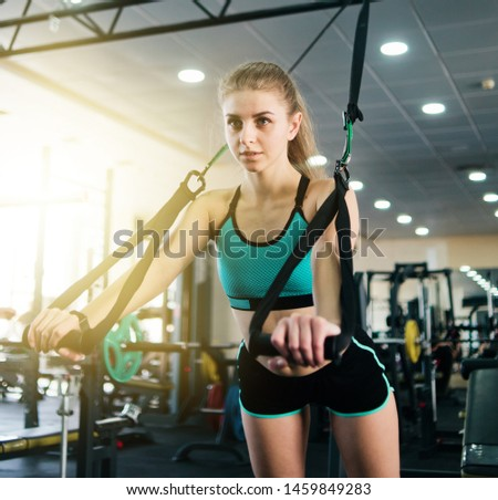 Fit woman in sportswear does push-up exercise with fitness straps in the gym. Functional training Stock foto ©