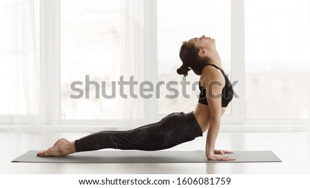 Fit woman making cobra pose on yoga mat, exercising in studio over panoramic window Сток-фото ©