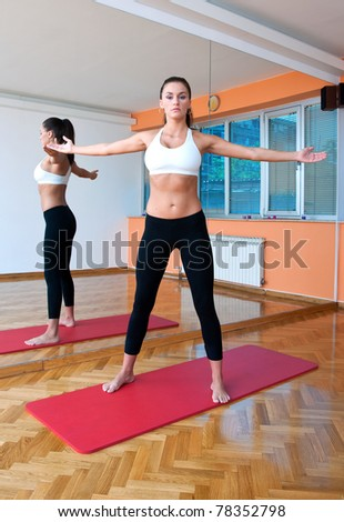 fit woman making warm up position in front of fitness studio mirror