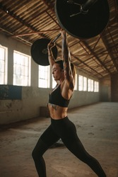 Fit woman performing  snatch workout with barbell in old warehouse. Strong female athlete with muscular body lifting weights.