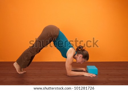 Fit woman practicing yoga with foam stability block