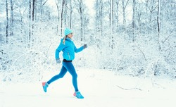 Fit woman running in winter and snow to do her sports exercise, sideways to camera