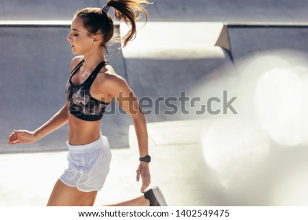 Fit woman running outdoors. Healthy young female athlete doing fitness workout.