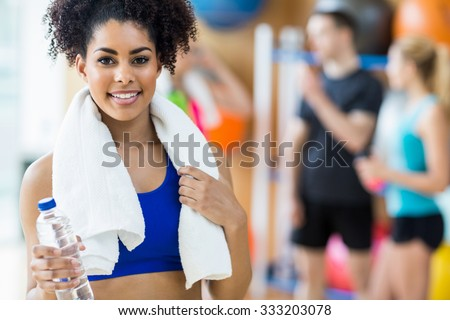 Fit woman smiling at camera at the gym
