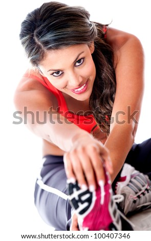 Fit woman stretching her leg - isolated over a white background