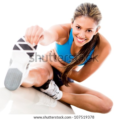 Fit woman stretching her leg to warm up - isolated over white background - stock photo
