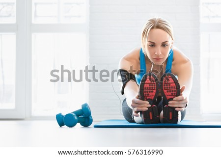 Fit woman stretching her leg to warm up on blue mat at home. Fitness concept, close up on sport shoes