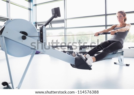 Fit woman training on row machine in gym