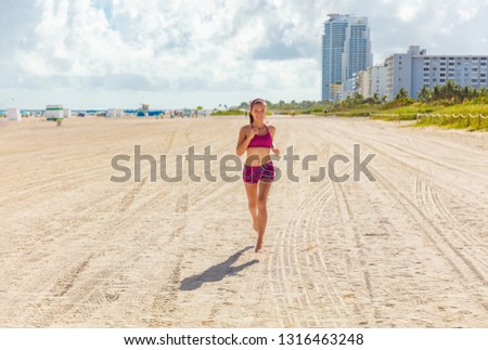 Fit woman training outdoors running barefoot on Miami south beach run jogging workout female Asian athlete. Happy healthy fitness person cardio jog in sun summer lifestyle. #1316463248