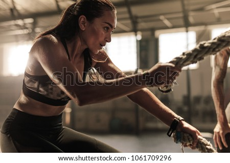 Fit woman using battle ropes during strength training at the gym. Athlete moving the ropes for burning fats at health club.