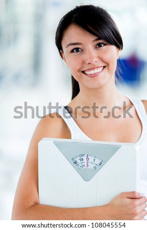 Fit woman with a scale at the gym