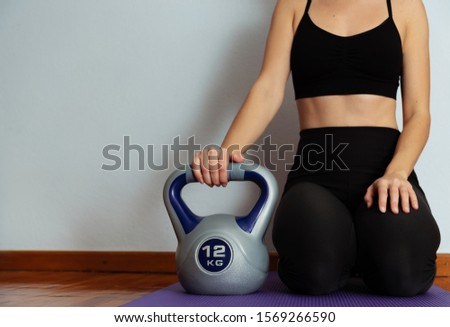Fit woman with sportswear sitting on mat and holding 12 kilogram kettlebell.