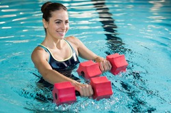 Fit woman working out with foam dumbbell in swimming pool. Woman engaged in doing aqua aerobics in water. Young beautiful woman doing aqua gym exercise with water dumbbell in swimming pool.