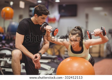 Fit woman working out with trainer at the gym
