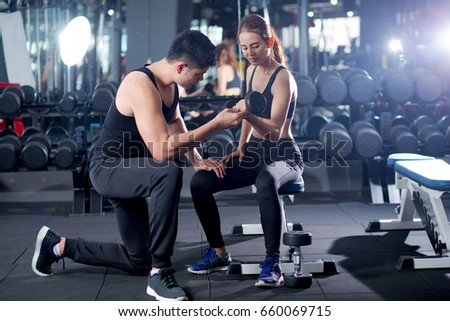 Fit woman working out with trainer at the gym, Gym equipment and sport concept, Dumbbells.