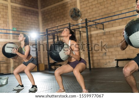 Fit women and man exercising with sports equipment while looking up during cross training at health club