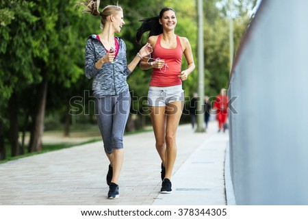 Fit women jogging outdoors and living a healthy lifestyle #378344305