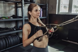Fit Women training with fitness trx straps in gym. Beautiful lady exercising her muscles with suspension straps.