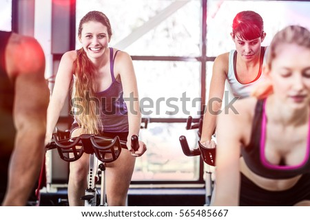 Fit women working out at spinning class in gym #565485667