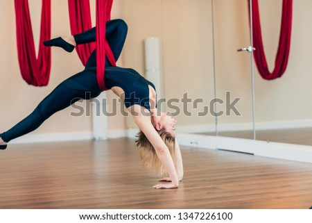 Fit yogini female diversifies her indoor workouts performing antigravity yoga exercises to normalize blood circulation, improve posture, develop flexibility and endurance of muscles.