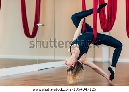 Fit yogini female diversifies her indoor workouts performing antigravity yoga exercises to normalize blood circulation, improve posture, develop flexibility and endurance of muscles. #1354047125