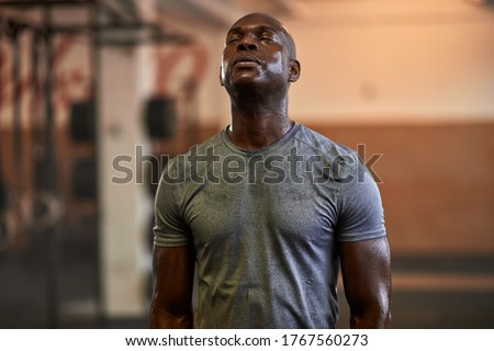 Fit young African American man standing with his eyes closed and sweating after a gym workout Сток-фото ©