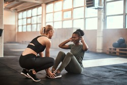 Fit young African American woman laughing while doing sit-ups with her friend during a workout at the gym
