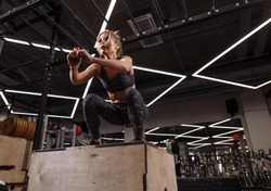 fit young ambitious blond woman doing a box jump exercise.hobby. side view full length photo. people concept