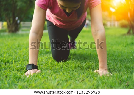Fit young asian woman practicing yoga plank pose, Exercising push ups at outdoor park in summer. Fitness female in sportswear and smart watch heart rate monitor tracker doing chest workout training. #1133296928