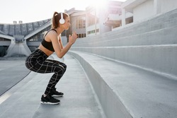Fit young attractive woman exercising in outdoor arena. Interval training by doing jumps and squats on stairs. Wearing sports active wear and headphones