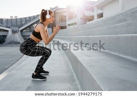 Fit young attractive woman exercising in outdoor arena. Interval training by doing jumps and squats on stairs. Wearing sports active wear and headphones Stock photo ©