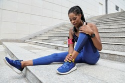 Fit young Black sportswoman suffering from pain in her ankle after morning jog