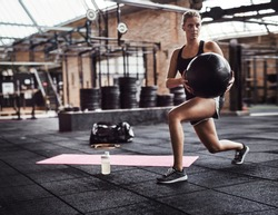 Fit young blonde woman in exercise clothing doing core exercises with an exercise ball while working out alone in a gym