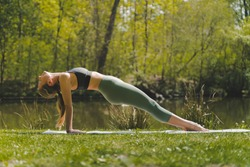 Fit young Caucasian blonde girl doing reverse plank on mat in nature in morning. Yoga practicing concept