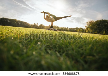 Fit young couple doing acroyoga on grass. Man and woman in park practising pair yoga poses. #534608878