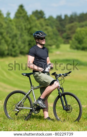 Fit young cycling man relax with water bottle in summer countryside