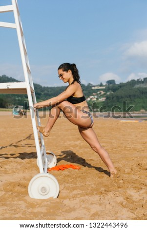 Fit young female athlete exercising and stretching at the beach on summer.