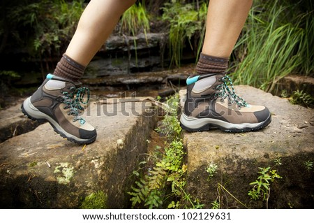 Fit young hiker crosses stone steps in hiking boots - stock photo
