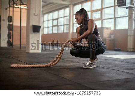 Fit young Indian woman in sportswear holding a battle rope while crouching on the floor of a gym Сток-фото ©
