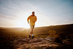 Fit young male athlete returning back after morning run on mountain trail