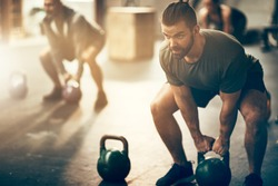 Fit young man in sportswear focused on lifting a dumbbell during an exercise class in a gym